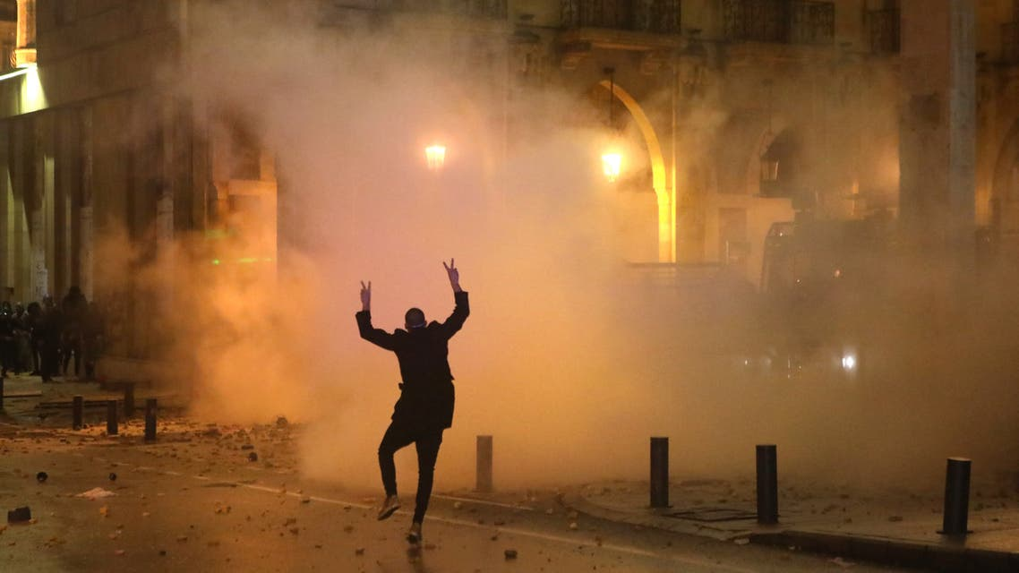Lebanese security forces fire tear gas canisters as they stand amidst tear gas clouds during clashes with anti-government protesters in the central downtown district of the Lebanese capital Beirut following clashes with anti-government protesters there on January 18, 2020.