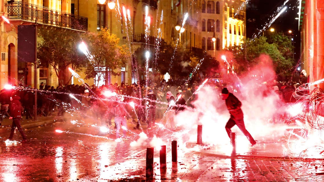 Protesters throw firecrackers at riot police during a demonstration against the new government in Beirut on Jan. 22, 2020. (AP)