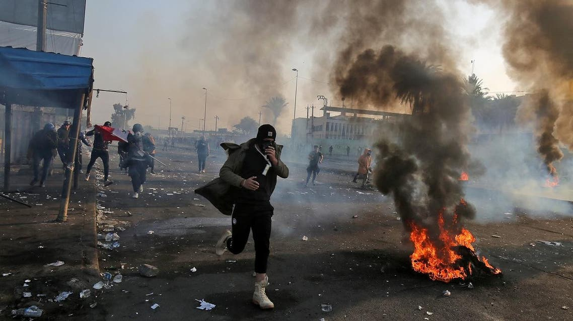 An anti-government protester wearing a gas mask runs hold his mask past flaming tires and through tear gas fumes at the scene of clashes with security forces in Tayaran Square. (AFP)