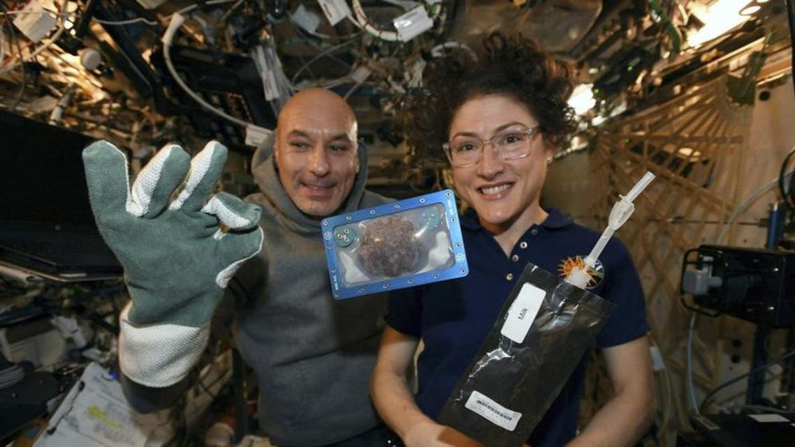 US astronaut Christina Koch and Italian astronaut Luca Parmitano pose for a photo with a cookie baked on the International Space Station on Dec. 26, 2019. (NASA)