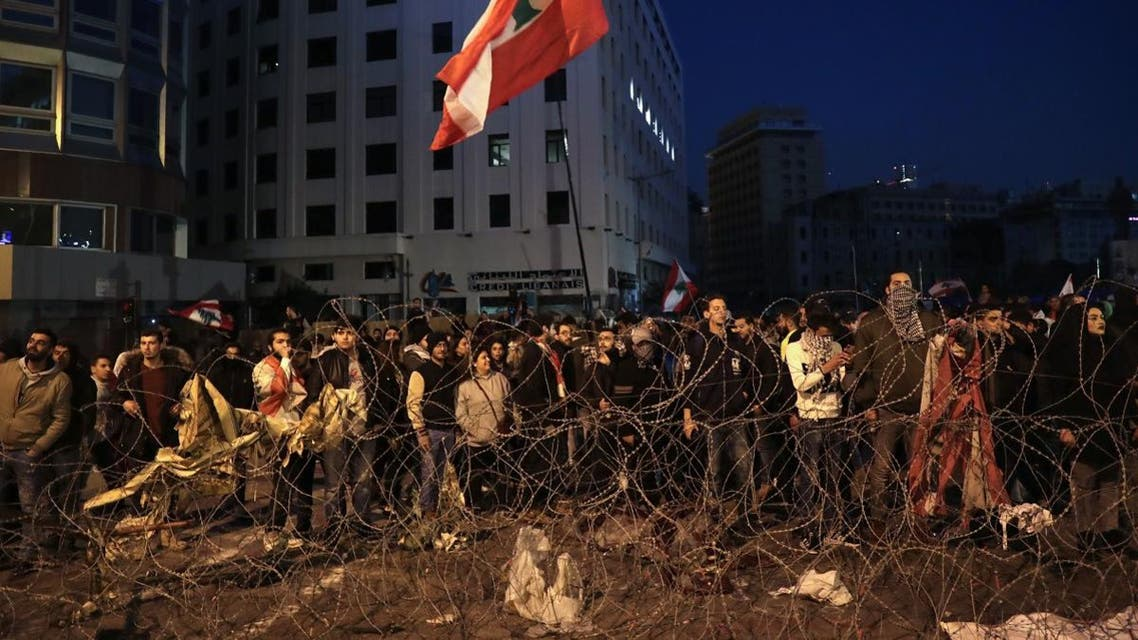 Lebanese anti-government demonstrators rally by barbed wire set by security forces to block a road leading to the government headquarters at the Grand Serail, in downtown Beirut, on January 25, 2020. (AFP)