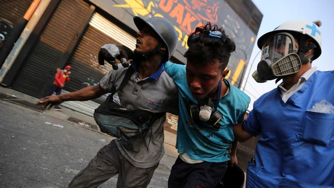 Opponents of Venezuela's President Nicolas Maduro aid a fellow demonstrator who was injured during the day's protests against government forces in Caracas, Venezuela, Tuesday, April 30, 2019. (AP)