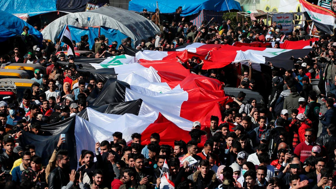 Anti-government protesters hold a huge Iraqi flag as they gather during a protest in Tahrir Square in Baghdad on Jan. 26, 2020. (AP)
