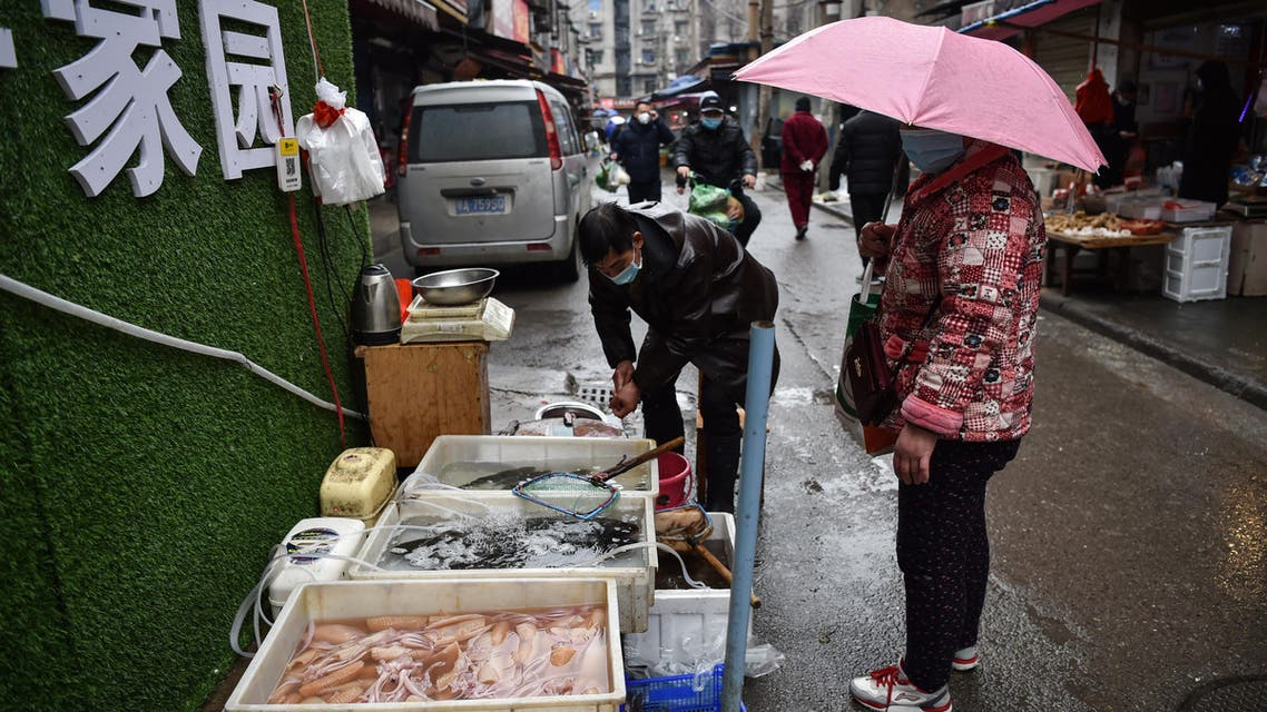 A masked vendor sells fish and turtles at a market in Wuhan where the coronavirus was discovered on January 24 2020. (AFP)