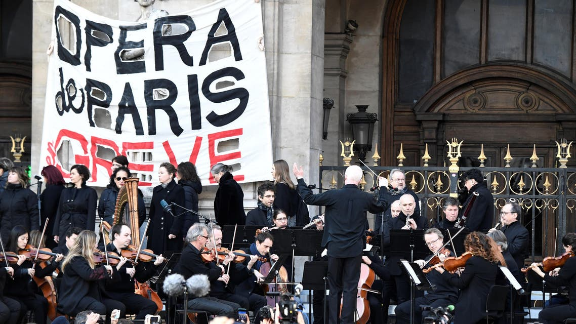 Musicians perform in front of the Palais Garnier during a demonstration of striking employees of the Opera Garnier and the Comedie Francaise, against the French government's plan to overhaul the country's retirement system in Paris (AFP)