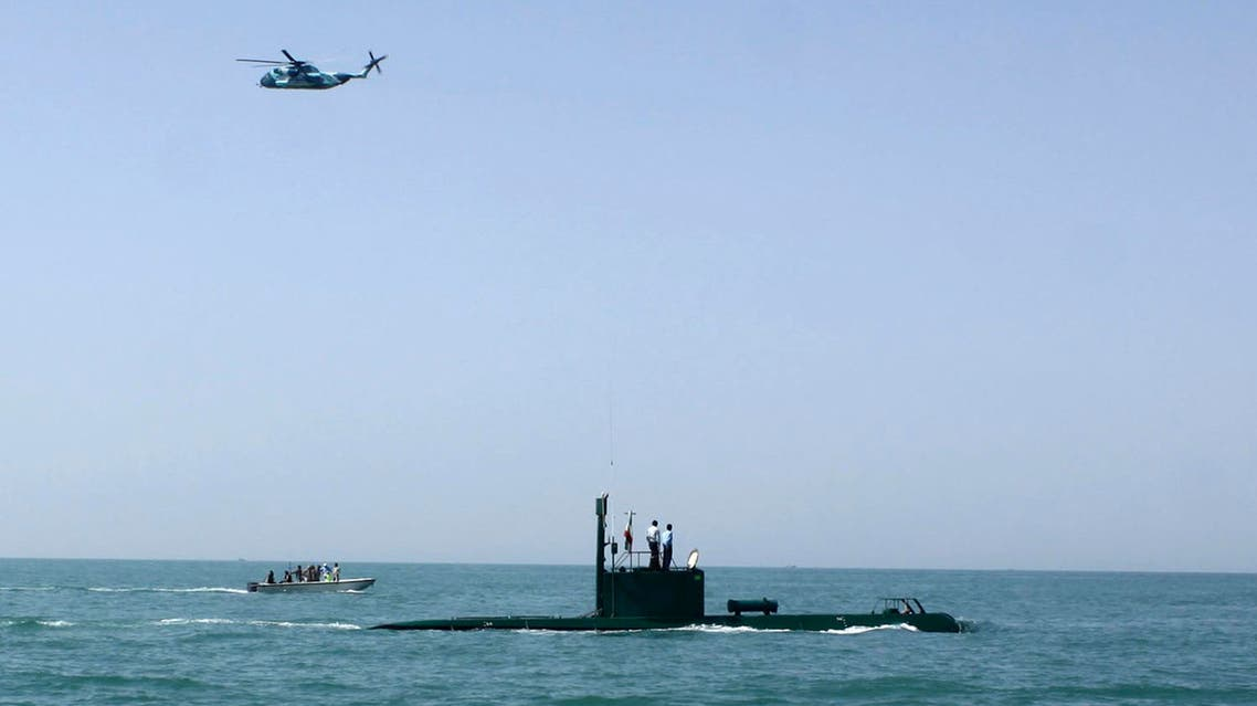 In this photo released by the semi-official Iranian Fars News Agency, a helicopter flies over a submarine during Iranian naval maneuvers in the Oman Sea in a part of Iranian southern waters (AP)