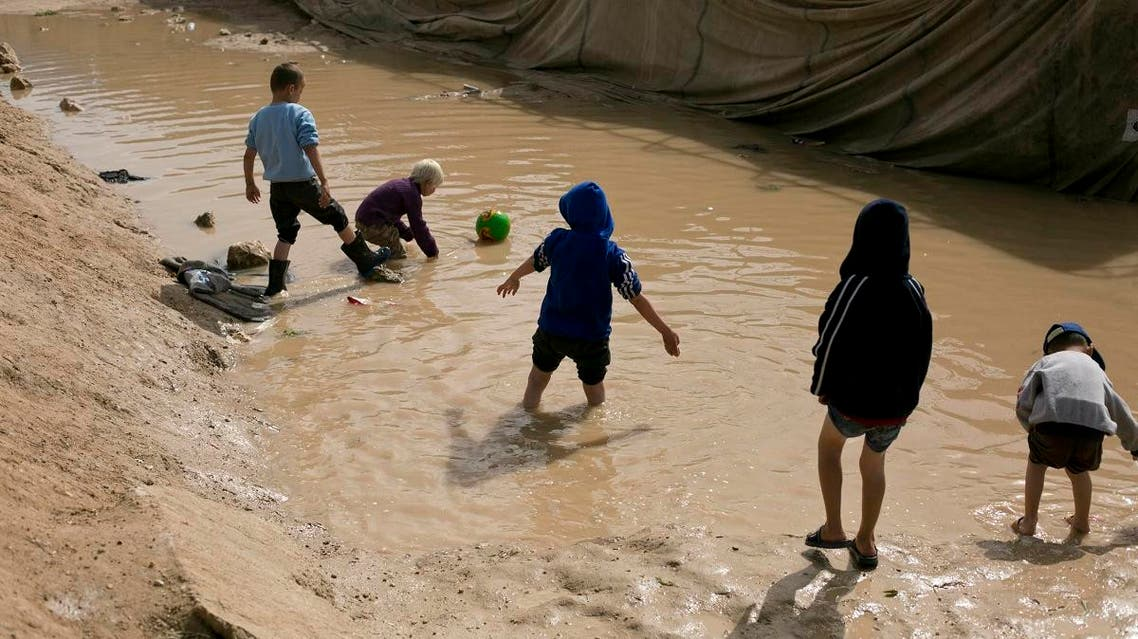 In this March 31, 2019, photo, children play in a mud puddle in the section for foreign families at Al-Hol camp in Hassakeh province, Syria. (AP)