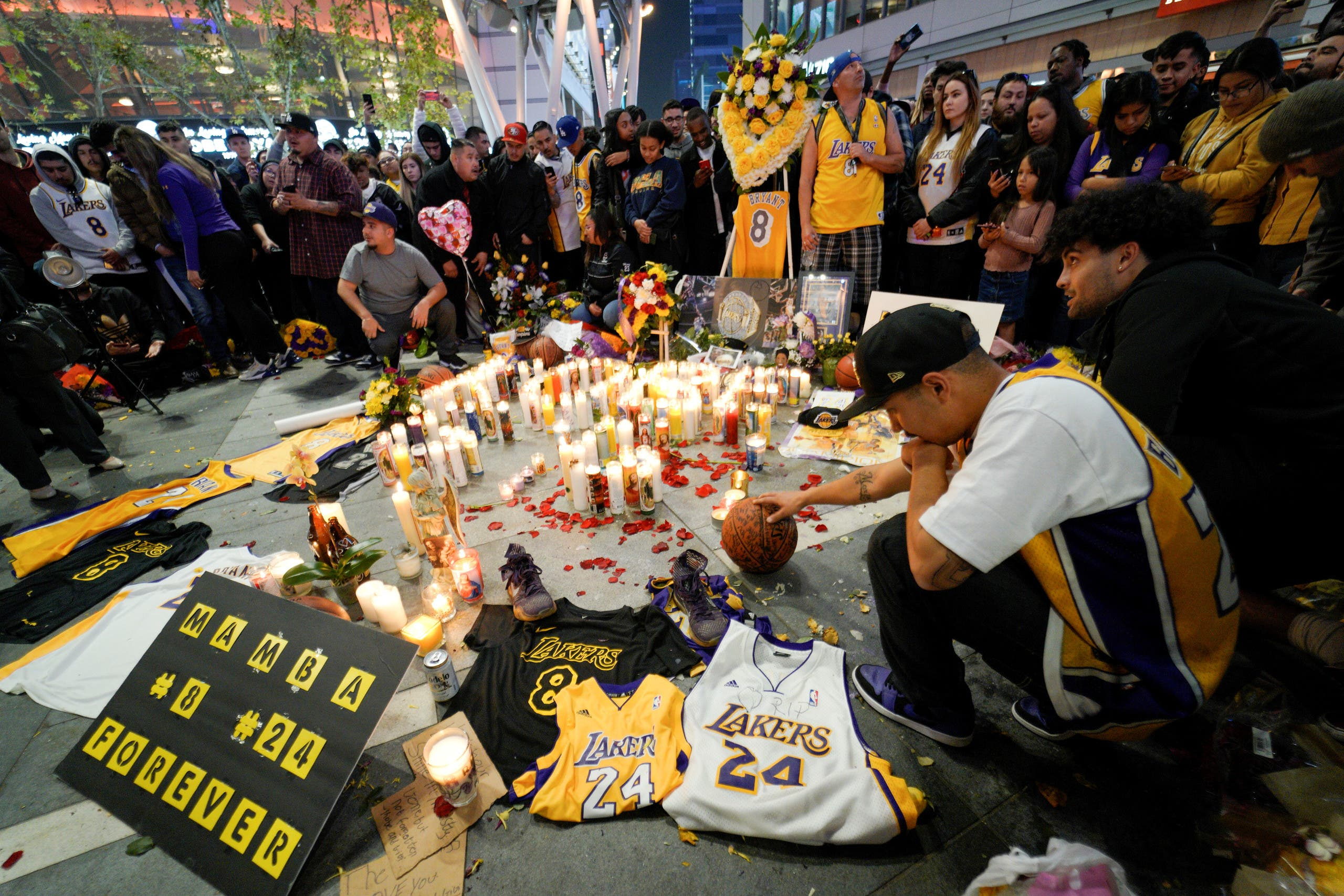 Mourners gather in Microsoft Square near the Staples Center to pay respects to Kobe Bryant after a helicopter crash killed the retired basketball star, in Los Angeles. (Reuters)