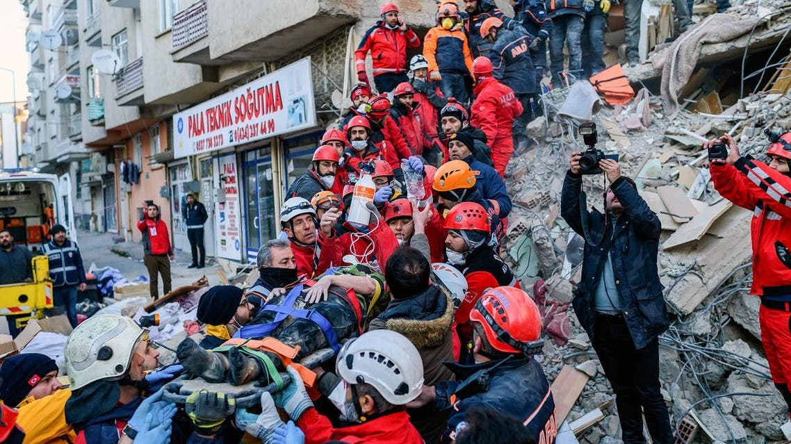 Rescue workers evacuate an injured woman from the rubble of a building after an earthquake in Elazig, eastern Turkey, on January 25, 2020. (AFP)
