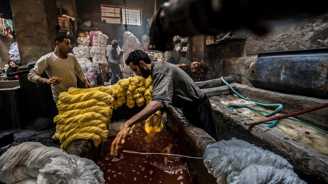 Workers dye yarns at a traditional hand-dying workshop in the Egyptian capital Cairo's centuries old district of Darb al-Ahmar on January 21, 2020. (AFP)