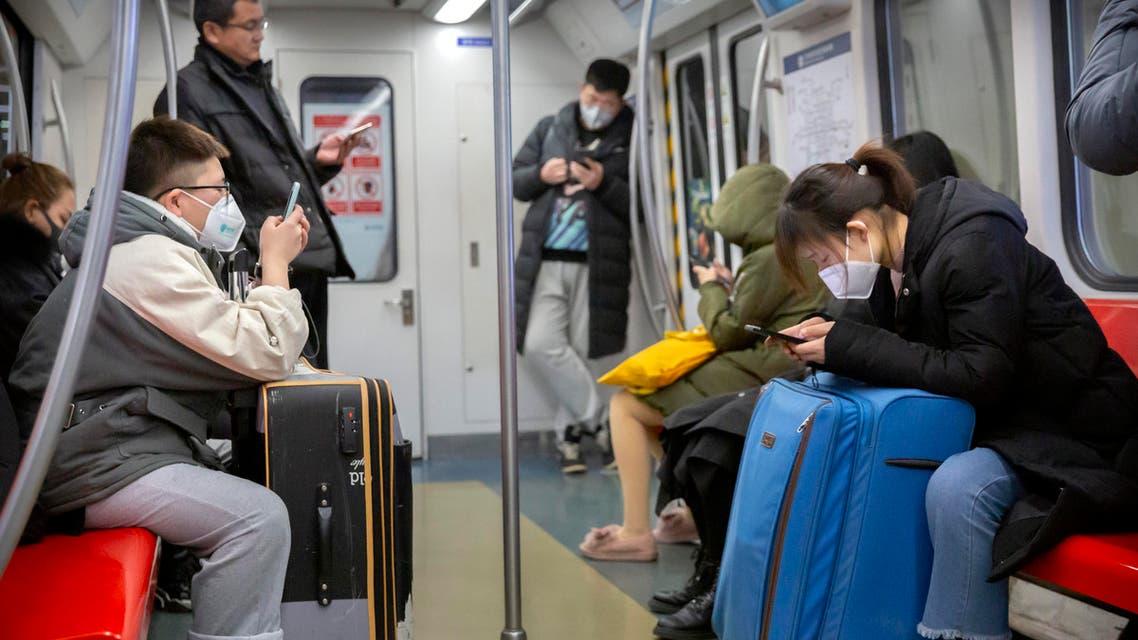 People wearing face masks ride a subway train in Beijing, Sunday, Jan. 26, 2020. (AP)