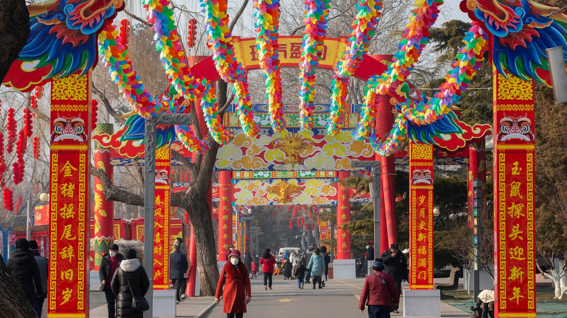 People wearing face masks walk under a canopy decorated with spinning colored fans for a canceled Lunar New Year temple fair at Longtan Park in Beijing. (AP)