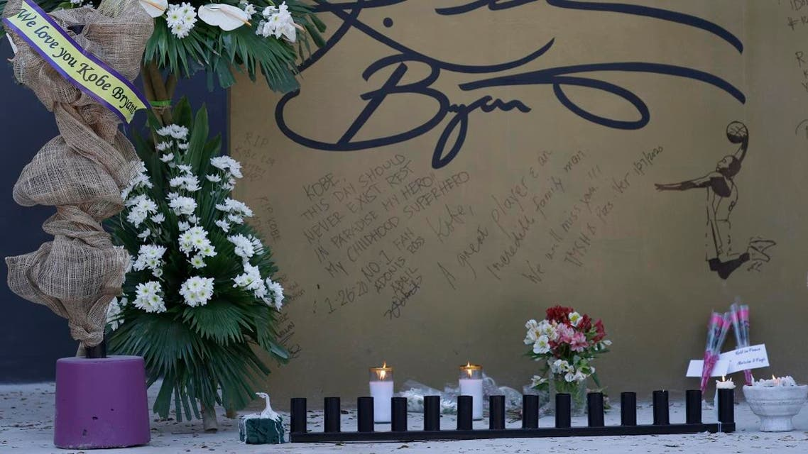 """Flowers and candles are left on the wall with a signature of former NBA basketball player Kobe Bryant at the """"House of Kobe"""" basketball court in Valenzuela, north of Manila, Philippines on Monday, Jan. 27, 2020. (AP)"""