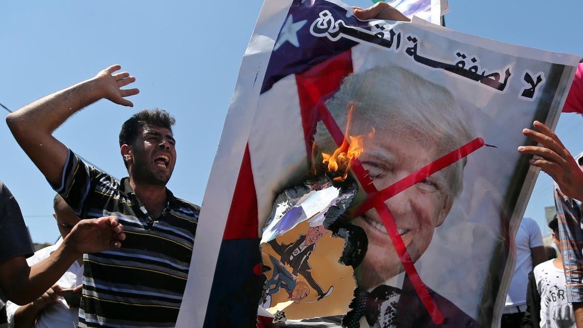 """Palestinian demonstrators burn a crossed-out poster depicting U.S. President Donald Trump and reading: """"no for Deal of the Century"""" during a protest against Bahrain's workshop for U.S. Middle East peace plan, in the southern Gaza Strip, June 26, 2019. (Reuters)"""