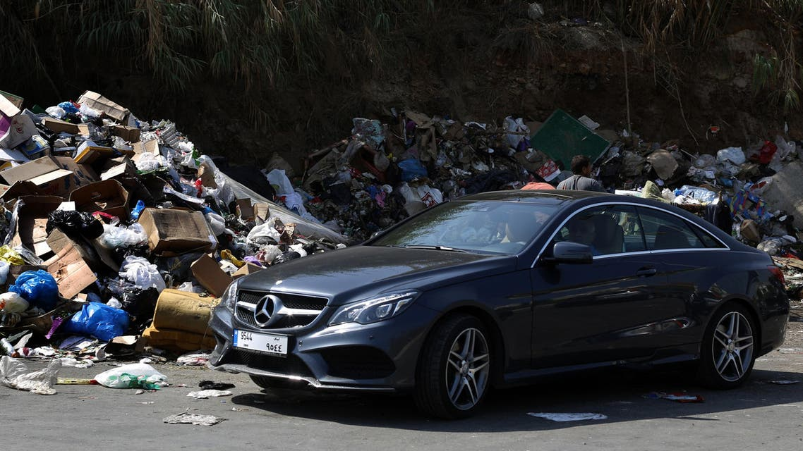 A man sits in his luxury car next to a garbage pile in a temporary dump in Beirut, Lebanon, on September 23, 2015. (File photo: AFP)