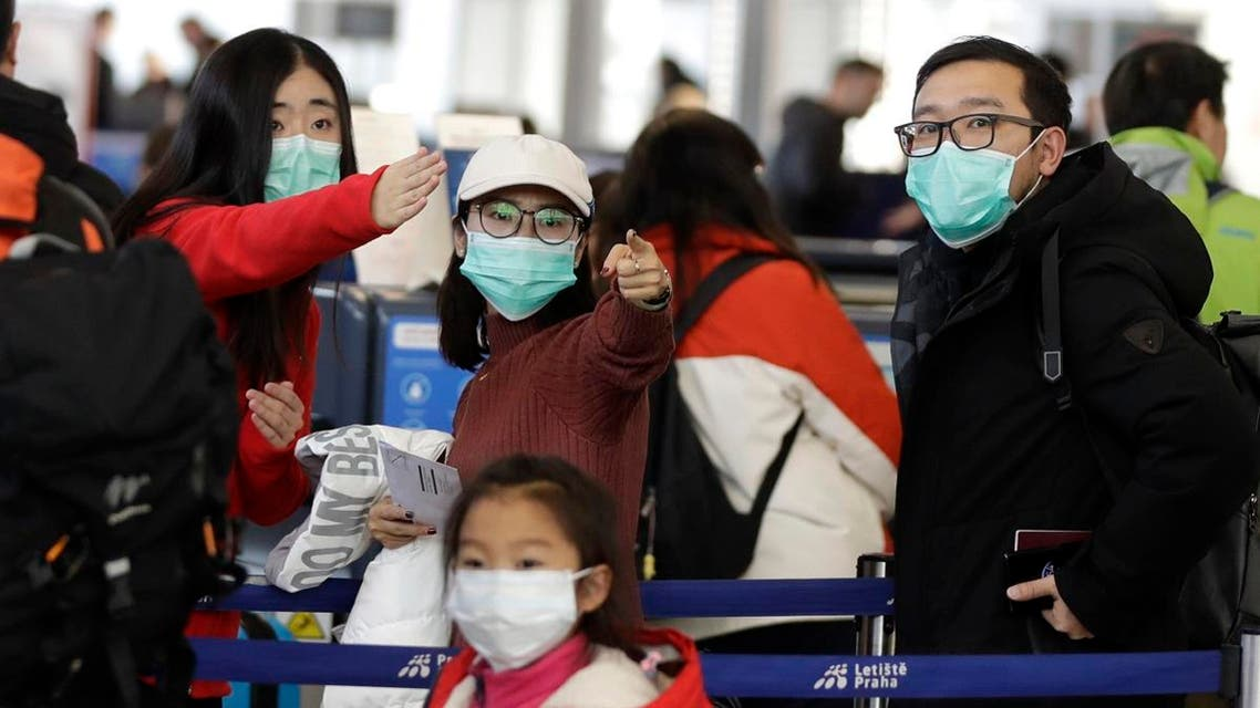 Passengers wearing masks wait in a line to check-in to a flight to Shanghai at the Vaclav Havel International Airport in Prague, Czech Republic, on January 27, 2020. (AP)