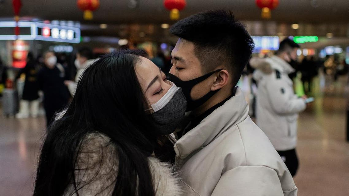 A couple, wearing protective masks, kisses goodbye as they travel for the Lunar New Year holidays, at Beijing West Railway Station in Beijing on January 24, 2020. (AFP)