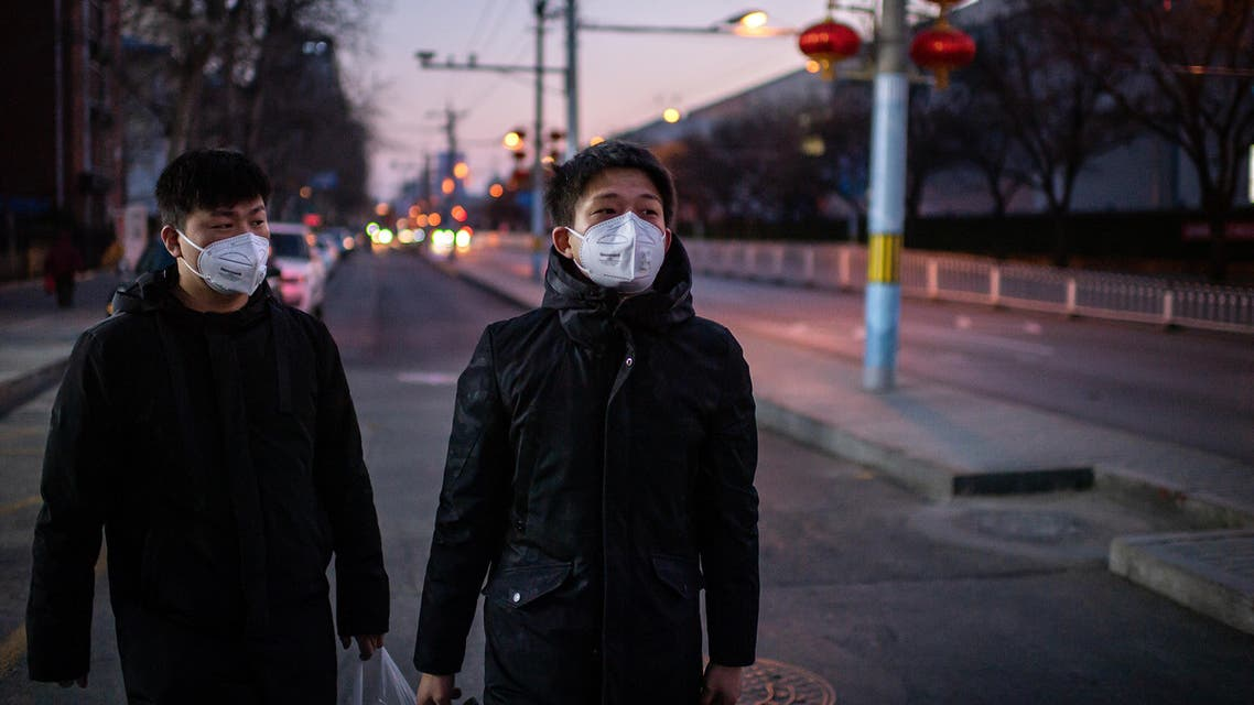 Young men, wearing protective face masks to help stop the spread of a deadly virus which began in Wuhan, as they walk on a street in Beijing on January 29, 2020. (AFP)