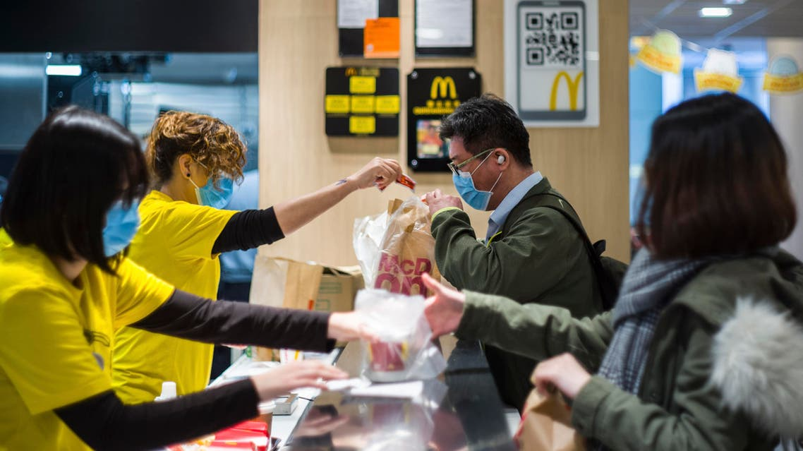 Members of staff (L) and customers (R) wear face masks at the counter of a MacDonald's fast food restaurant in Hong Kong. (AFP)