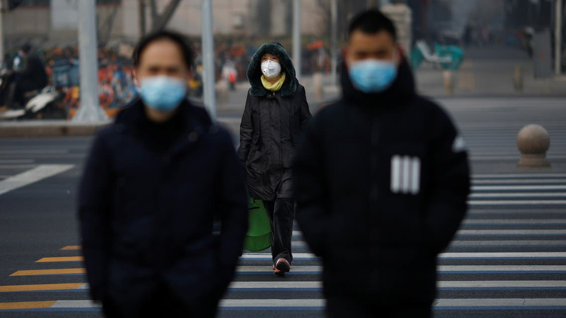 People wearing masks walk across a street as the country is hit by an outbreak of the new coronavirus, in Beijing, China January 28, 2020. REUTERS/Carlos Garcia Rawlins