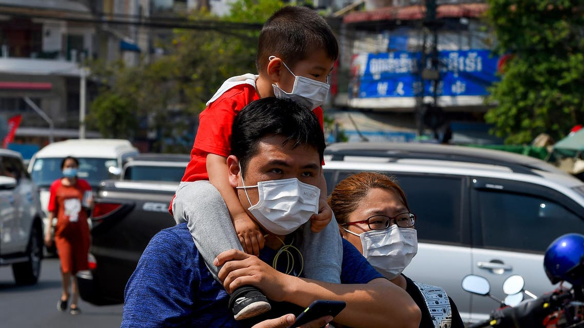 A family wear face masks as they walk along a street in Phnom Penh on January 29, 2020. (File photo: AFP)