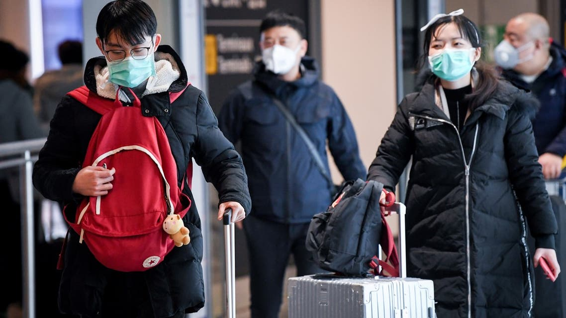 Passengers coming from China, leaves the Terminal wearing paper masks after landing in Charles De Gaulle Airport on January 26, 2020 in Roissy-en-France. China expanded drastic travel restrictions to contain a viral epidemic that has killed 56 people and infected nearly 2,000, as the United States and France prepared to evacuate their citizens from a quarantined city at the outbreak's epicentre.
