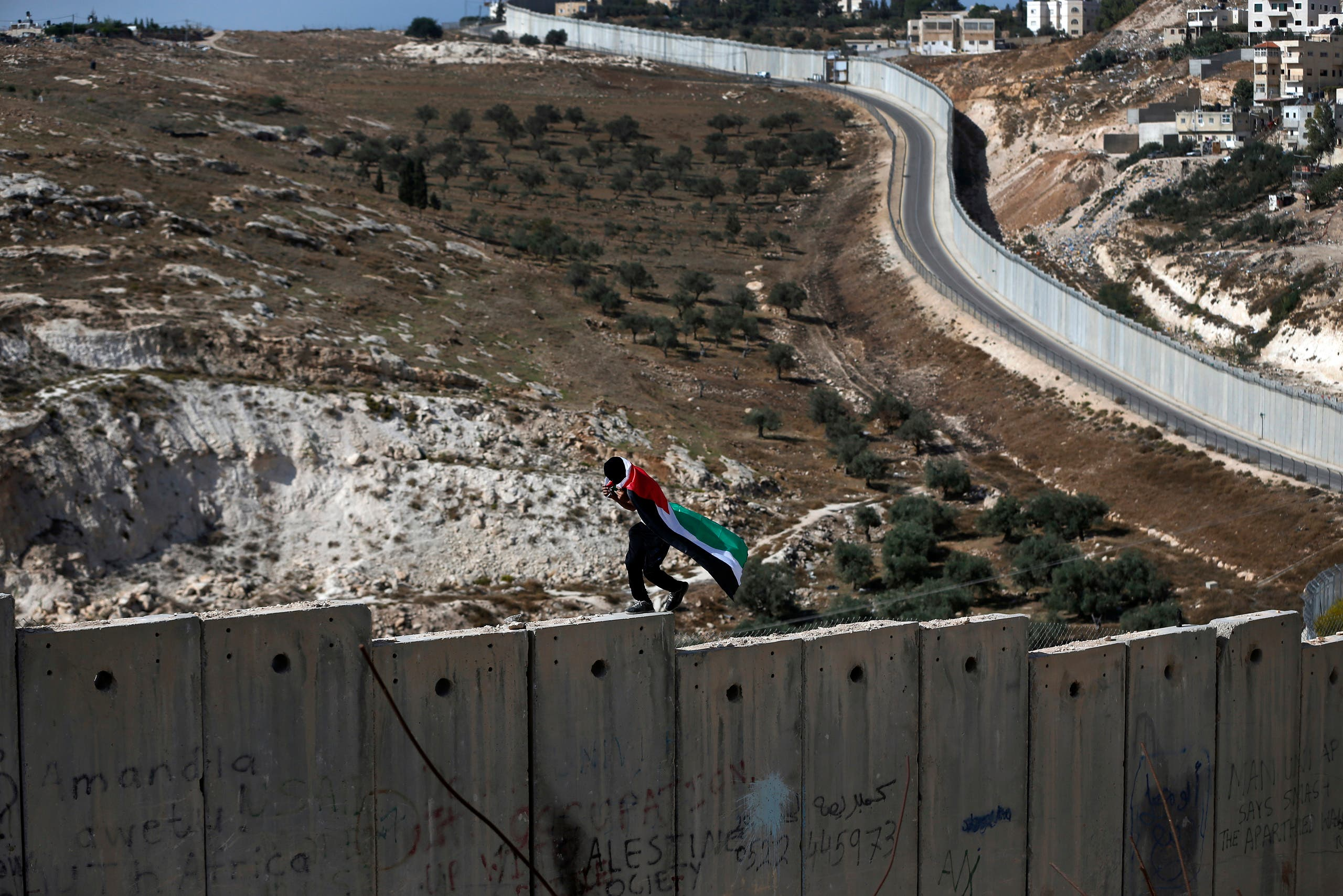 A Palestinian covered with national flag walks on top of the Israeli wall separating the West Bank city of Abu Dis from east Jerusalem. (File photo: AFP)
