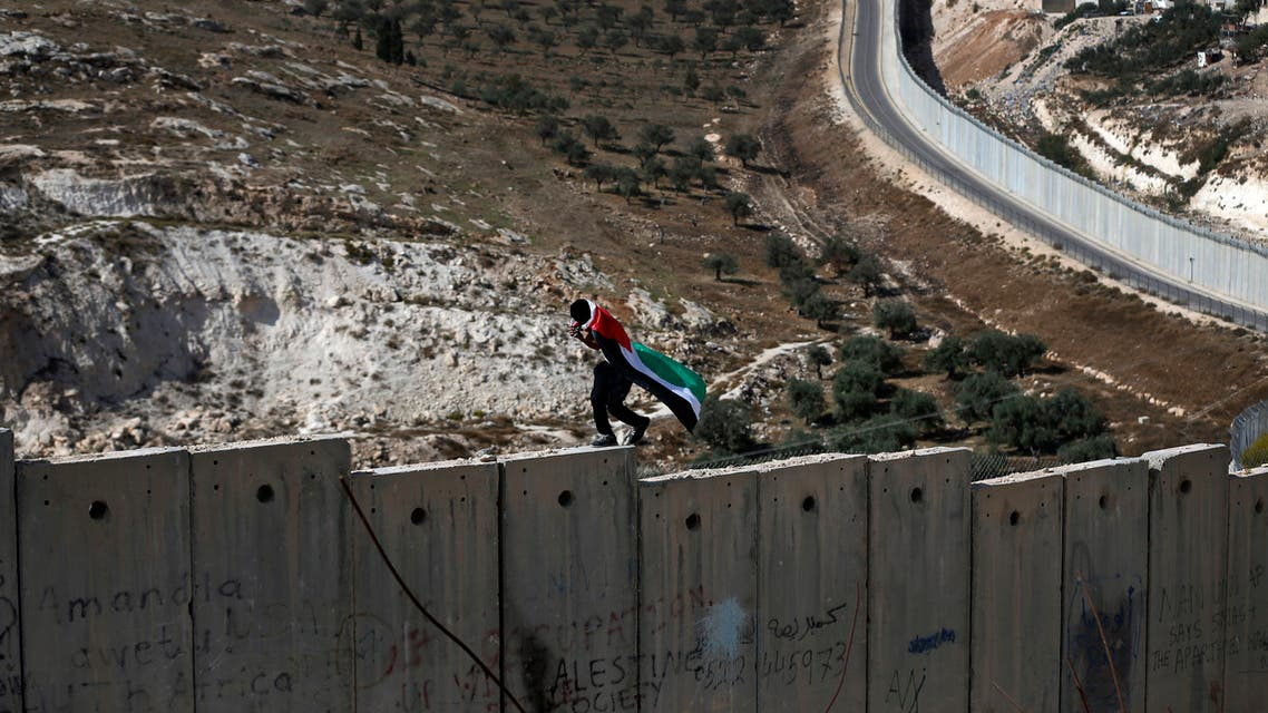 A Palestinian covered with national flag walks on top of the Israeli controvertial separation wall separating the West Bank city of Abu Dis from east Jerusalem, during clashes with Israeli security forces, on November 2, 2015. AFP HOTO / AHMAD GHARABLI
