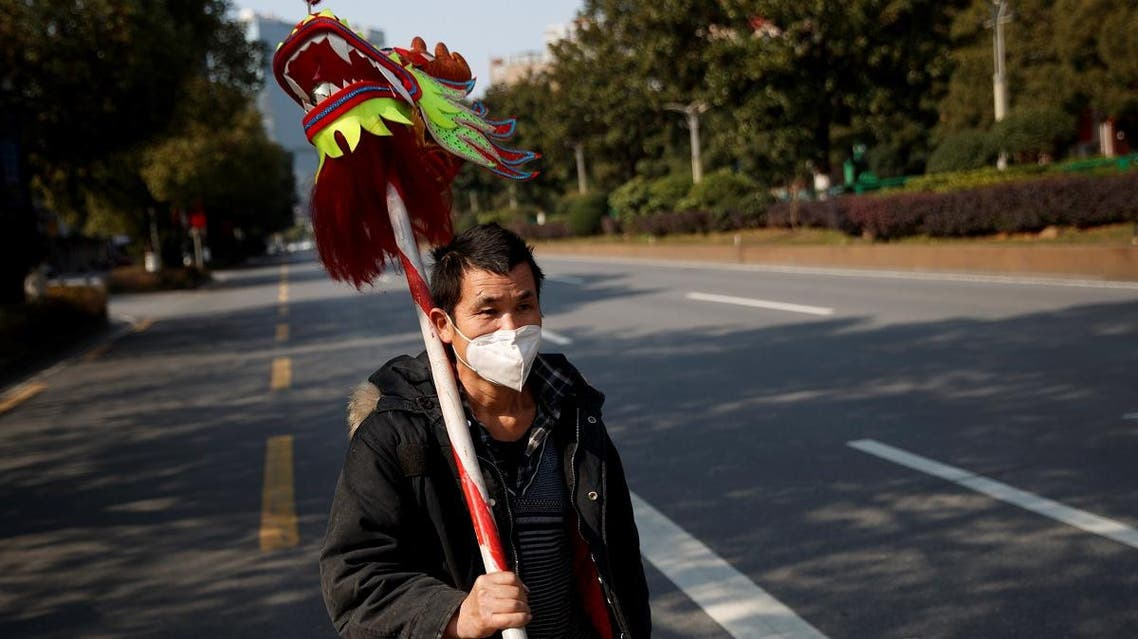 A man wearing a face mask carries the head of a dragon dance costume as he walks in the middle of an empty street in Changsha, Hunan province, China. (Photo: Reuters)