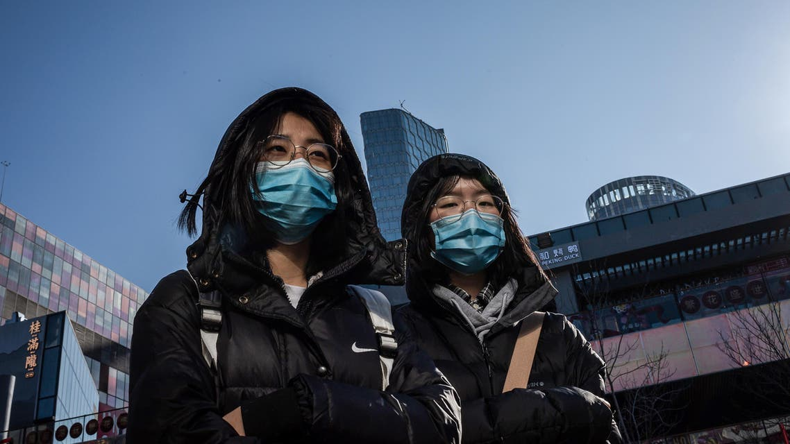 People wear protective masks as they walk outside a shopping mall in Beijing on January 23, 2020. China is halting public transport and closing highway toll stations in two more cities in Hubei province, the epicentre of a deadly virus outbreak, authorities said on January 23. NICOLAS ASFOURI / AFP