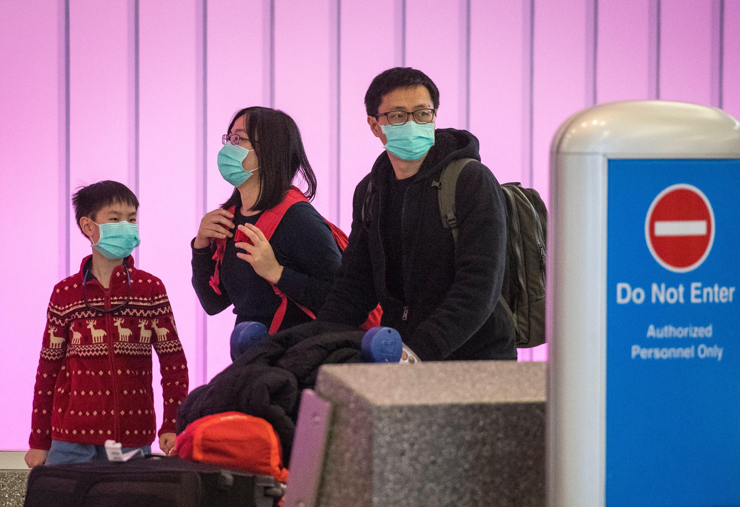 مسافرون يرتدون الأقنعة خوفاً من كورونا خلال تواجدهم في أحد المطارات الأميركية قادمين من آسيا(فرانس برس)