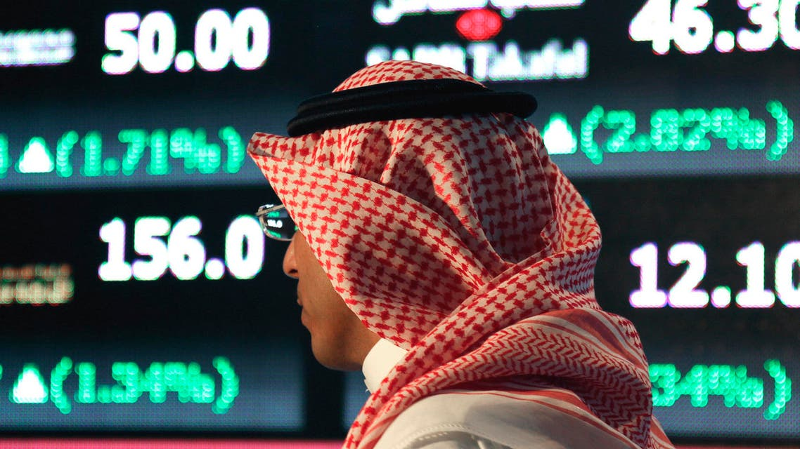Monday, June 15, 2015 file photo, a Saudi man walks at the Tadawul Saudi Stock Exchange, in Riyadh, Saudi Arabia. King Salman announced the approval for the Vision 2030 plan in a short televised announcement on Monday in which he called on Saudis to work together ensure its success. (AP Photo/Hasan Jamali, File)