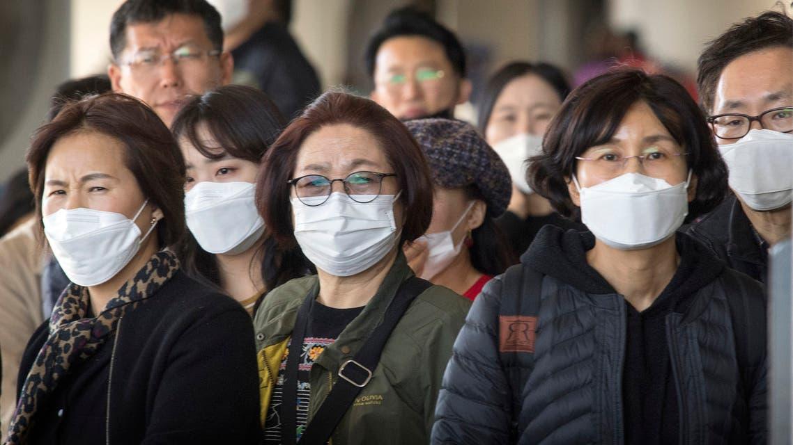 مسافرون يرتدون الأقنعة خوفاً من كورونا خلال تواجدهم في أحد المارات الأميركية قادمين من آسيا(فرانس برس)