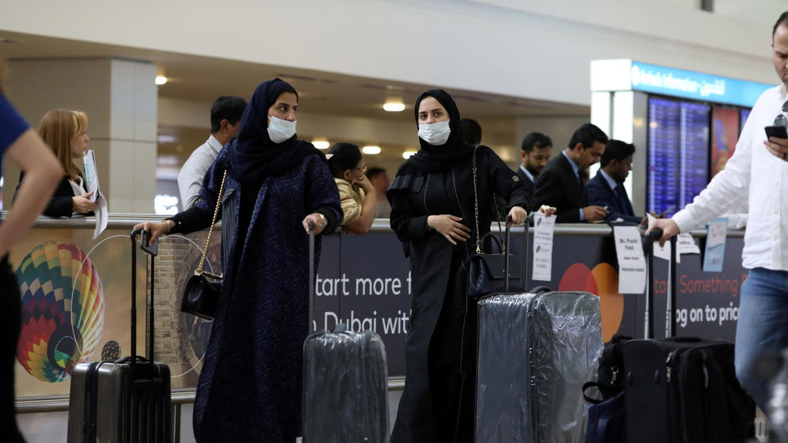 Travellers wear masks as they arrive at the Dubai International Airport, after the UAE's Ministry of Health and Community Prevention confirmed the country's first case of coronavirus, in Dubai, United Arab Emirates. (AP)