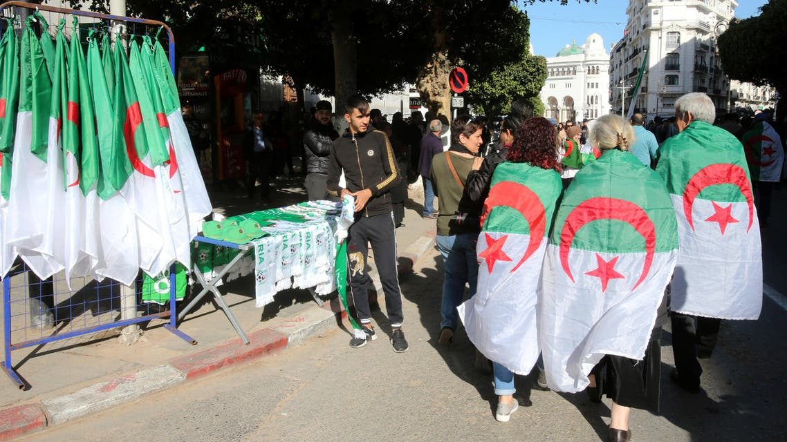 ALGERIA-PROTESTS/RTS2ZQ4A24 Jan. 2020Algiers, AlgeriaDemonstrators wearing national flags walk past a street vendor during a protest demanding a change of the power structure in Algiers, Algeria January 24, 2020. (Reuters)