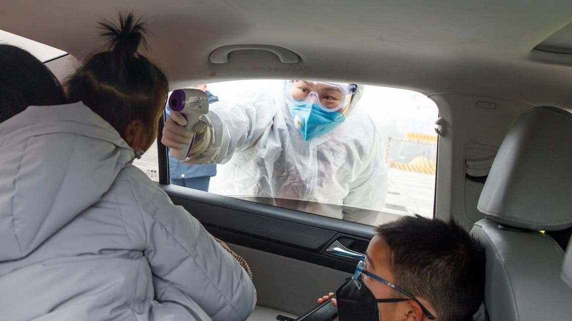 A medical worker in protective suit checks the body temperature of a car passenger at a checkpoint outside the city of Yueyang. (Reuters)