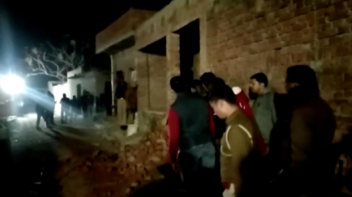 Residents and police personnel stand outside the building where a man has held hostages in Farrukhabad, Uttar Pradesh, India January 30, 2020 0 in this still image taken from video. ANI via REUTERS TV