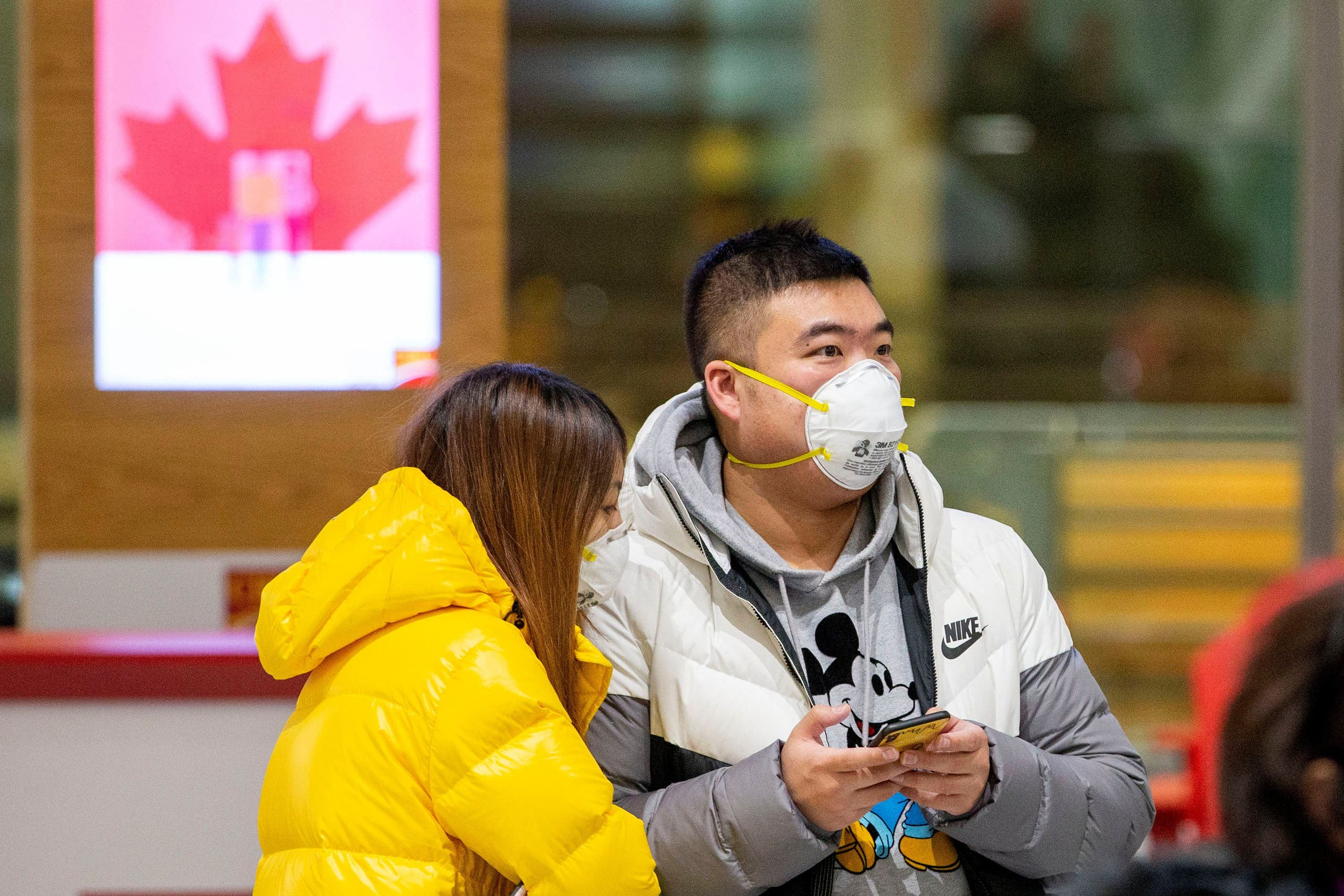 People waiting for passengers wear masks at Pearson airport arrivals, shortly after Toronto Public Health received notification of Canada's first presumptive confirmed case of coronavirus, in Toronto. (Reuters)