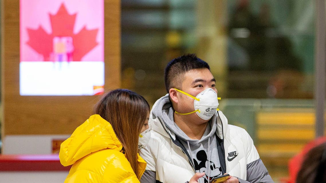 People waiting for passengers wear masks at Pearson airport arrivals, shortly after Toronto Public Health received notification of Canada's first presumptive confirmed case of coronavirus, in Toronto (Reuters)