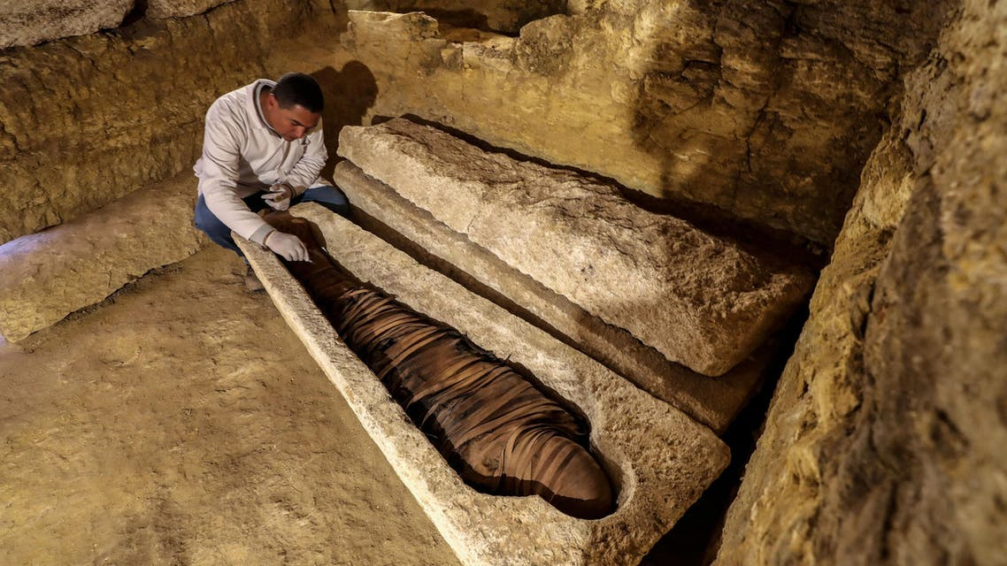 An Egyptian archeologist inspects a mummy in a limestone sarcophagus discovered along many finds in 3000-year-old communal tombs dedicated to high priests (AFP)