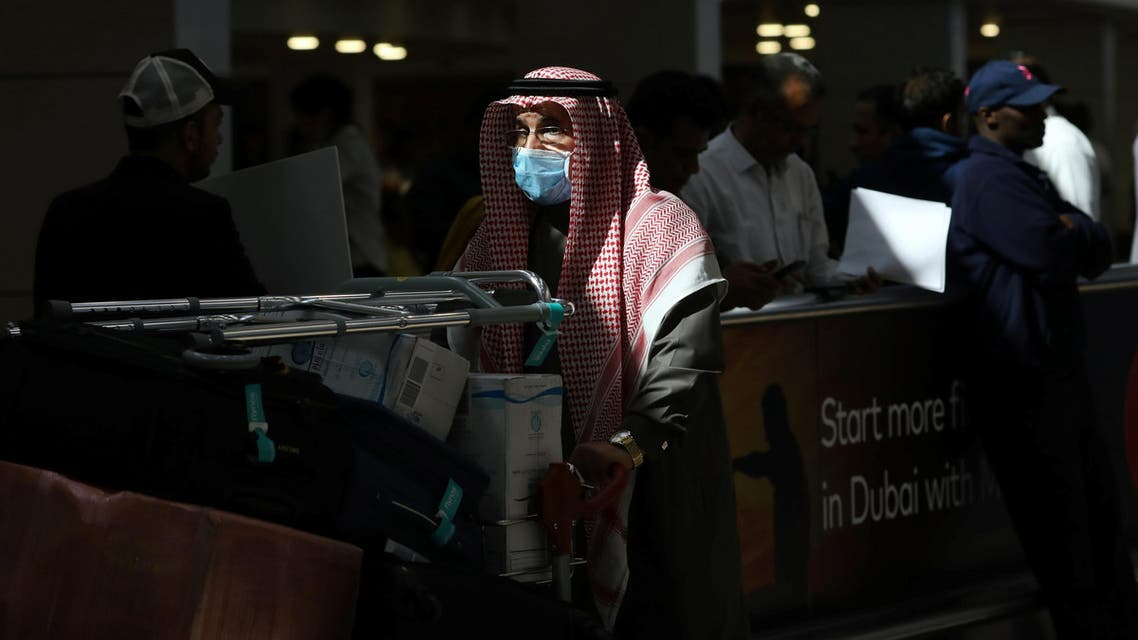 A traveller wears a mask as he pushes a cart with luggage at the Dubai International Airport, after the UAE's Ministry of Health and Community Prevention confirmed the country's first case of coronavirus. (Reuters)
