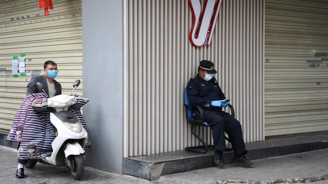 A security officer wearing a face mask checks his phone while sitting outside a closed shop in China. (Reuters)