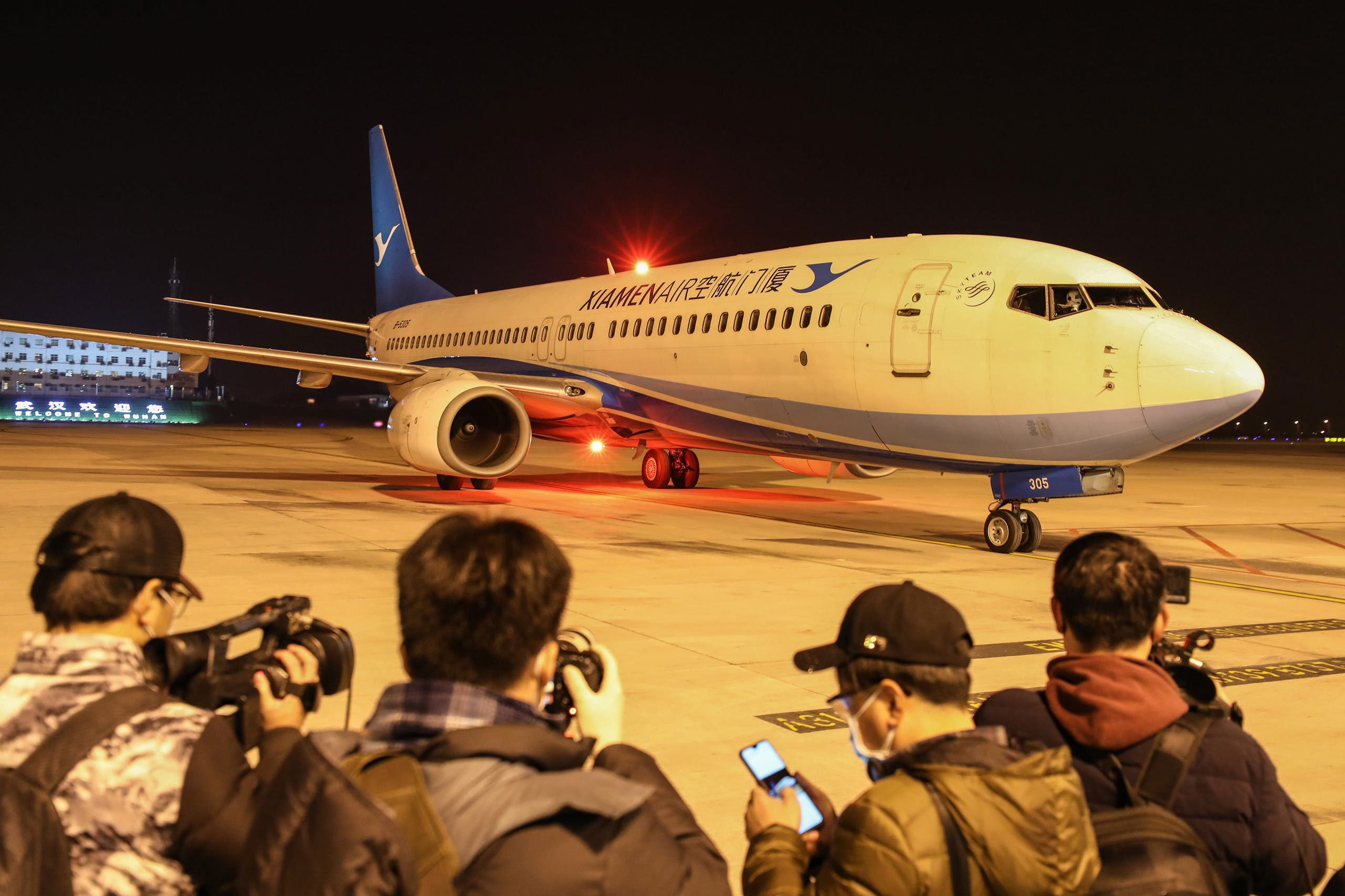 journalists waiting as a plane of Xiamen Airlines carrying Hubei residents arrives from the Thai capital Bangkok (AFP)