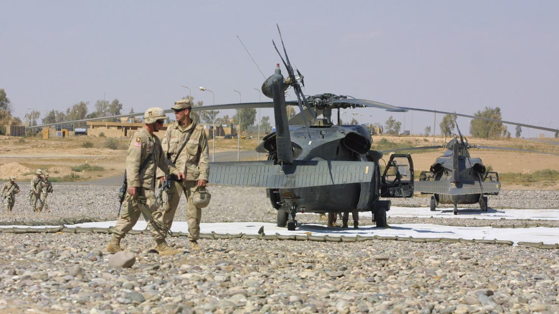 US troops from the 101st Airborne Division walk past Blackhawks at an airbase in Qayyara, 35 kms south of Mosul, in nothern Iraq on their way for lunch break at the base's cafeteria 04 October 2003. The United States has about 130,000 troops in Iraq, almost all from the US Army, the service that has been most stressed by the demands of occupying Iraq while keeping sufficient forces ready for other contingencies, according to a spokesman for the US Central Command at its headquarters in Tampa, Florida. AFP PHOTO/Ahmad AL-RUBAYE