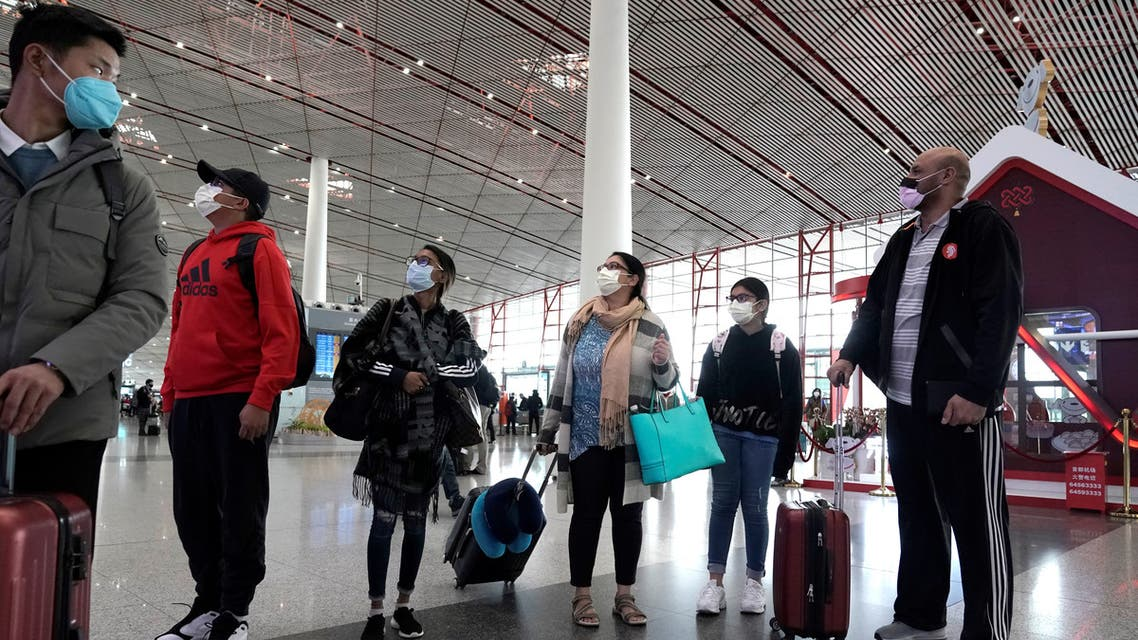 Foreign travellers wearing masks check their flight's departure information at Beijing International Airport in Beijing, China as the country is hit by an outbreak of the new coronavirus, February 1, 2020. REUTERS/Jason Lee