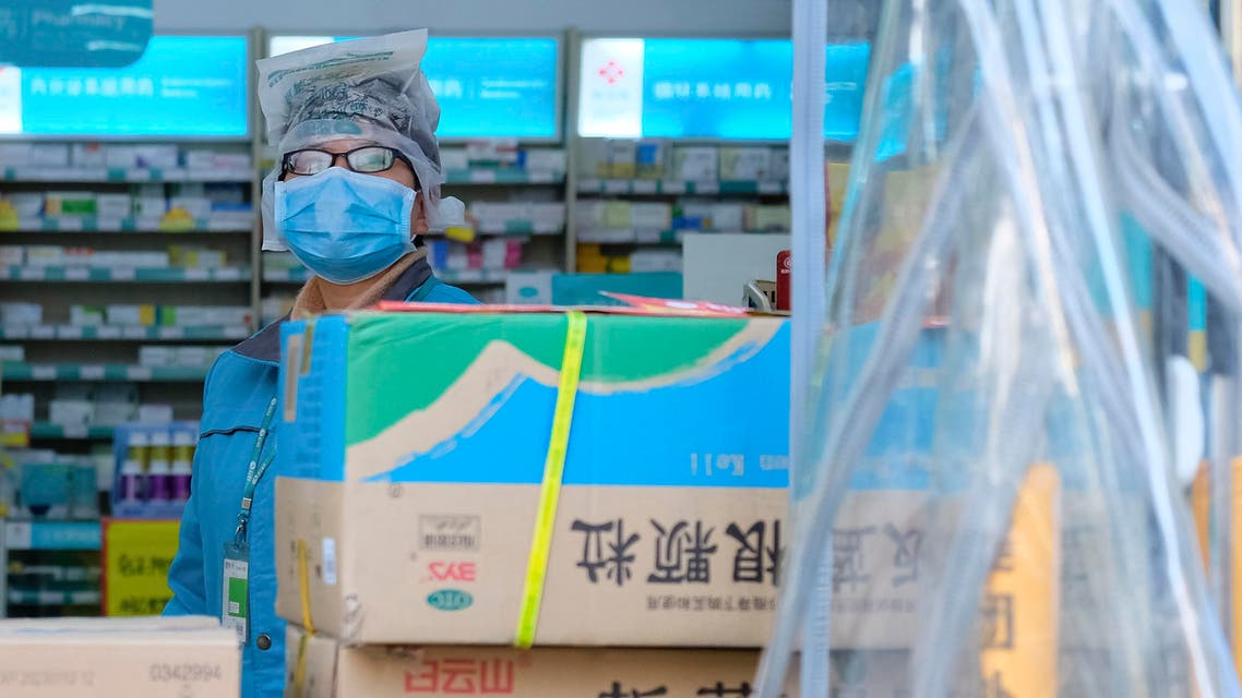 A clerk wearing a face mask and a plastic bag stands in a pharmacy in Wuhan in central China's Hubei Province. (AP)