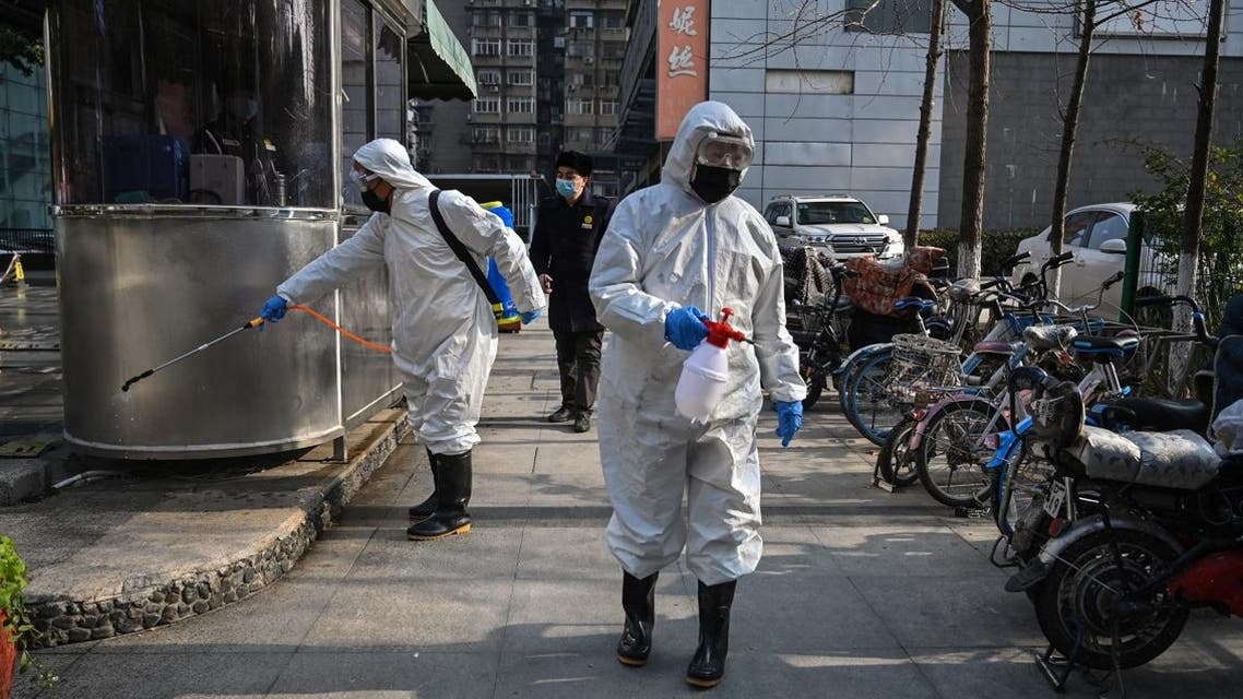 People dressed in protective clothes disinfect an area in Wuhan, in Hubei province on January 30, 2020. (AFP)