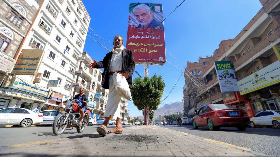 A Yemeni man walks beneath a poster of slain Iranian military commander Qasem Soleimani in the capital Sanaa, on January 8, 2020. Soleimani and and Iraqi paramilitary chief Abu Mahdi al-Muhandis were killed in a US drone strike near Baghdad's international airport on January 3, sparking fury in Iran and Iraq.