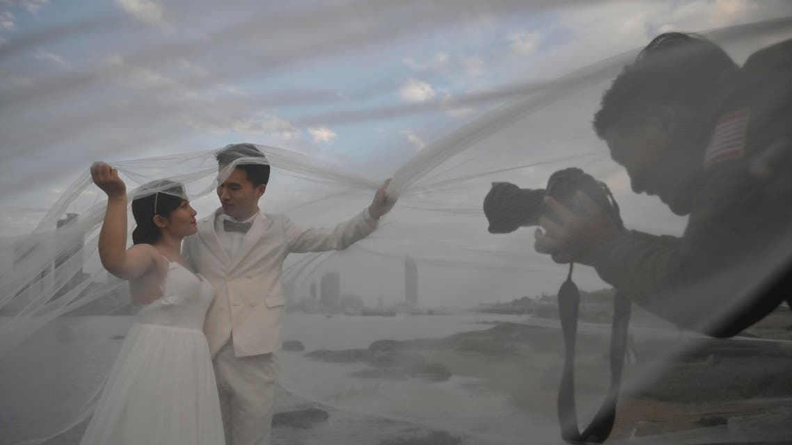 A couple poses for a wedding photographer in Gulangyu Island in Xiamen of Fujian province. (AFP)