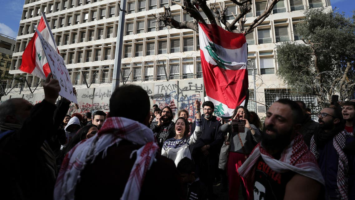 CORRECTS PHOTOGRAPHER CREDIT TO HASSAN AMMAR Anti-government protesters chant slogans, during ongoing protests against the Lebanese government in front of the Central Bank, in Beirut, Lebanon, Saturday, Feb. 1, 2020. (AP Photo/Hassan Ammar )